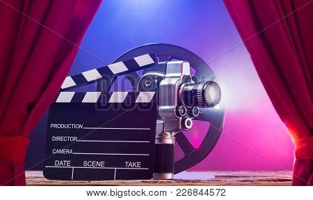 Illuminated Movie Camera With Clapperboard And Film Reel Against Colored Background