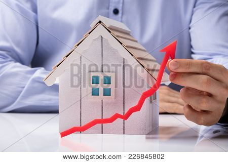 Person Holding Arrow In Front Of House Model