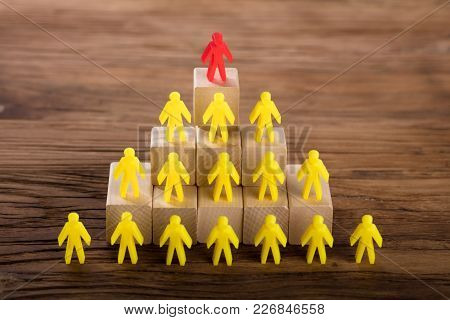 Red Figure Standing On Top Of Yellow Human Figures Over Wooden Blocks