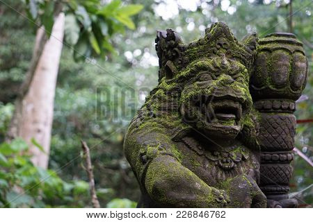 Mossy Statue In Bali Indonesia With Jungle And Palm Trees In The Back