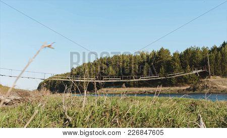Wooden Bridge And Field. Video. A Small Wooden Bridge Over A Creek. Grass, Blue Sky, Reeds. A Wooden