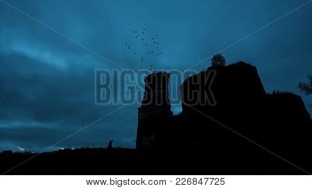 Mystical Silhouette Of A Temple Or Castle Against The Cloudy Sky And Ravens Flying In The Sky At Nig