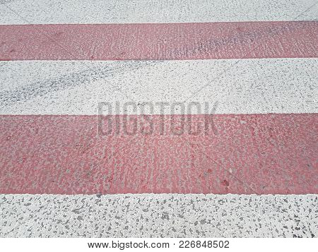 Pedestrian Crossing On The Road, Alternating Stripes Of Paint Red And White, Urban Background.