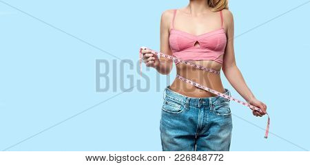Diet Concept. Woman Is Measuring Waist After Weight Loss On Faded Pastel Background