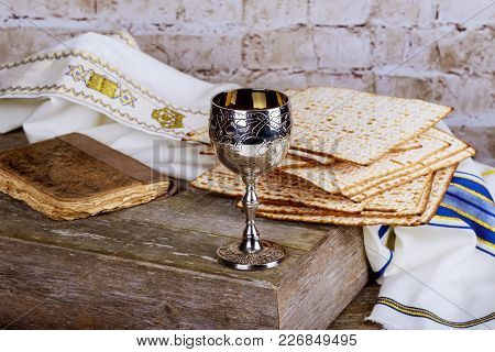 Glass Of Passover Wine And Matzah Close Up. Backlit Blurred Matzah Texture In Background.