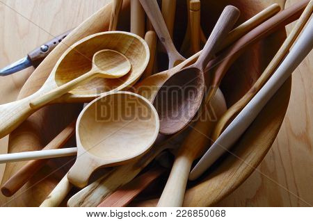 Pile Of Hand Carved Wooden Spoons In A Wooden Bowl Showing Their Lovely Wood Grain.