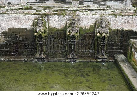 Holy Spring In Bali Indonesia With Mossy Statues
