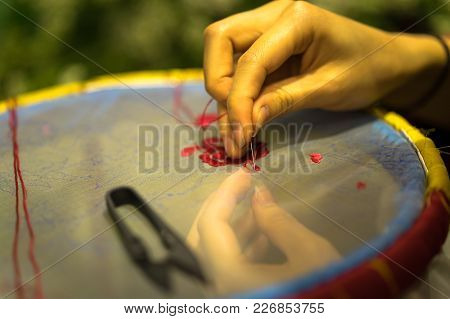 Female Hand Embroiders In The Hoop Under Lamp Light