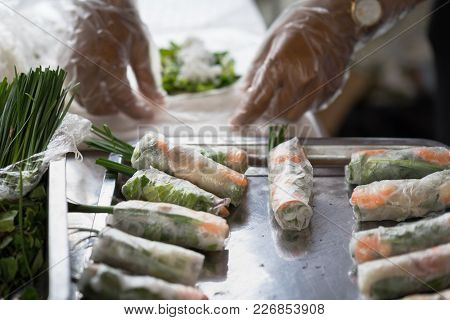 Fresh Spring Rolls With Shrimps With Cooker Hands On Background