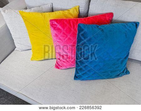 Bright Multicolored Cushions Decorating A Simple Gray Sofa.