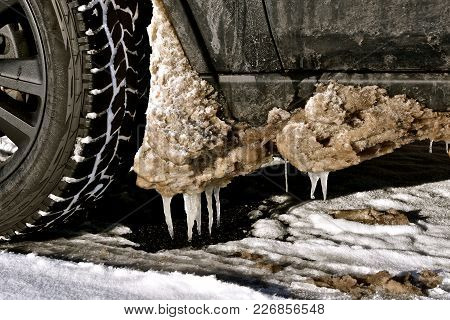 Mud, Snow, And Slush Thrown From A Car Front Tire Is Melting And Creating Icicles.