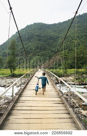 Vietnamese Hmong Ethnic Minority Boy Walking On Old Wooden Bridge With His Bicycle