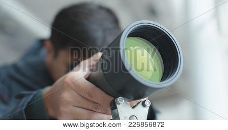 Man looking through telescope to observe the bird habitat