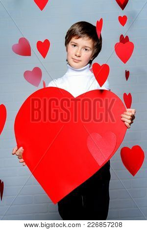 Ð¡ute pre-teen boy holding big heart surrounded by little hearts. First love. Valentine's Day.