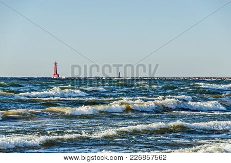Sunlit Waves Rushing Toward Shore With Navigational Aids In The Background.