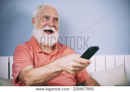 Excited Senior Man With White Beard Using Remote Control To Switch Channels
