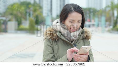 Young woman reading on mobile phone in the park