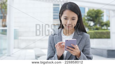 Business woman use of mobile phone in city