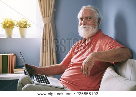 Portrait Of Handsome Elderly Man Sitting On Sofa In Domestic Room And Holding Open Laptop On His Lap