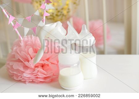 Breast Pump And Baby Bottles With Milk, Various Festive Paper Decor And Balloons In Front Of Baby Be