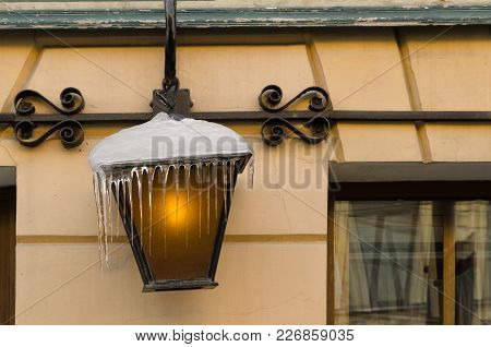 A Few Icicles Hang From A Street Lamp. The Lamp In The Lamp Is On. In The Background, The Wall Of Th