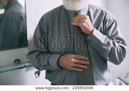 Elegant Senior Man With White Beard Adjusting His Necktie