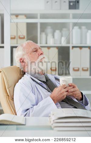 Tired Elderly Doctor Relaxing Over Cup Of Tea In His Office