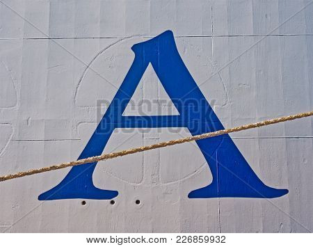 Blue Letter A On Boat Moored In Harbor On A Sunny Day.