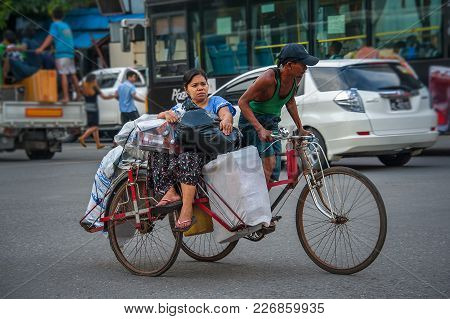 China Town, Yangon - Oct 21, 2017: A Tricycle Taxi Carrying A Passenger And Her Many Plastic Bags Fu