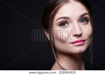 Headshot Of Young Attractive Caucasian Woman With Professional Make-up Looking At Camera On Dark Bac