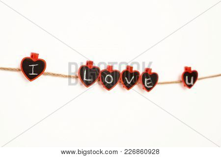 Clothes Pegs With I Love You Phrase Written With Chalk Attached To Rope On White Background