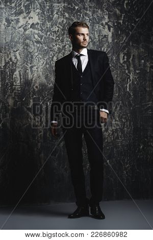 Full length portrait of a handsome man in an elegant suit on a grunge background. Studio shot.