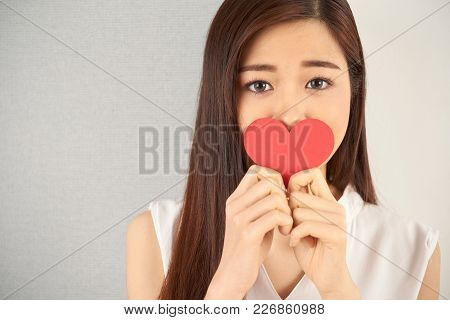 Beautiful Young Woman With Sad Eyes Holding Red Heart-shaped Valentine Card