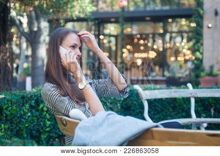 Stylish Young Smiling Woman Sitting On The Bench Outside, Talking On The Mobile Phone, City Street W