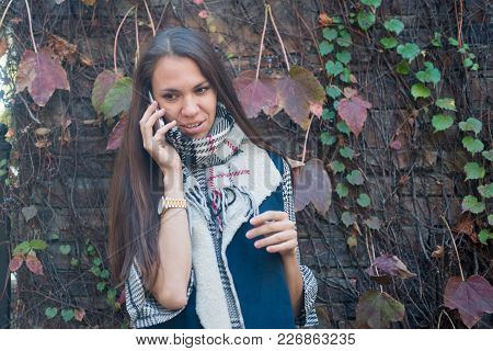 Young Woman Standing Outside, Talking On Her Mobile Phone, Smiling, Vine Leaves On Background
