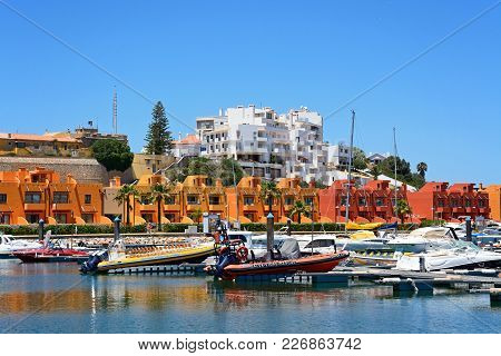 Portimao, Portugal - June 7, 2017 - Yachts And Motorboats Moored In The Marina With Apartments To Th