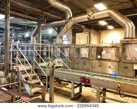LONDON - FEBRUARY 12, 2018: Automatic kegging equipment robotic machinery production line for filling metal kegs with beer at Fuller's Brewery in Chiswick, West London, UK.