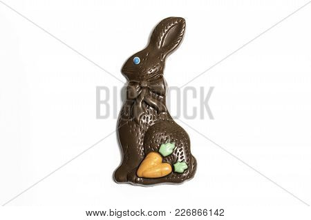 Chocolate Easter Bunny With Bue Eyes And Carrots On A White Background