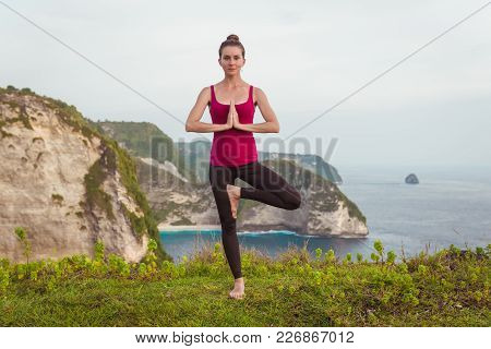 Yoga Woman. Tree Pose On Cliff And Ocean Background