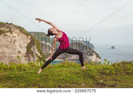 Young Woman Doing Yoga On Cliff Coast Of Ocean