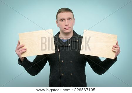 Cheerful Young Man Is Holding In Hands A Two Empty Wooden Boards With Copy Space. Billboard.