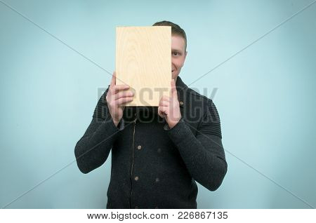 Happy Man Hides His Face Behind A Wooden Plaque Plate In His Hands And Peeks Out From There Isolated