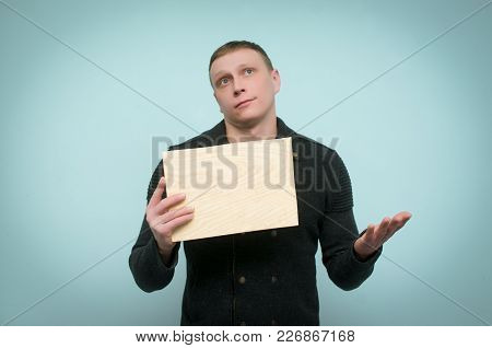 Pensive Man Is Holding In Front Of Him A Wooden Board With Copy Space And Is Thinking Isolated On Bl