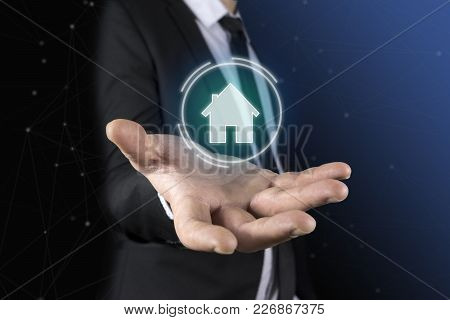 To A Man In A Suit And Tie Appears In His Hands A Futuristic Graphic Of The House. Concept Of: Home