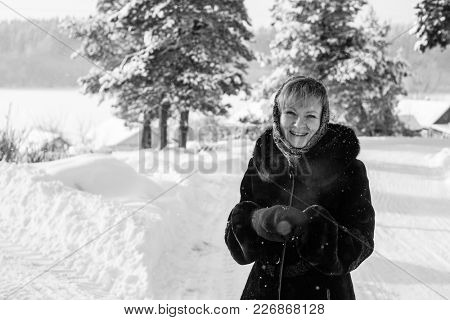 Young russian woman in a snowy village in winter. Black-and-white photo.