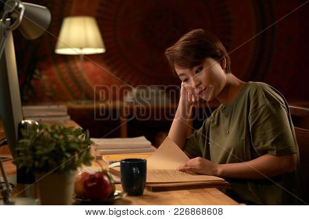Adult Asian Student Reading Textbook Late At Night At Home