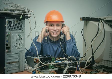 Computer Repairman Is Talking On Phone Handset And Is Installing A New Computer Component. Pc Servic
