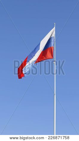 The National Flag Of Russia Fluttering On A Flagstaff Against The Background Of The Clear Blue Sky.