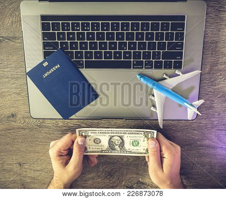 Concept - No Money For A Travel. Hands Hold One Dollar With Background Laptop, Passport And Airplane