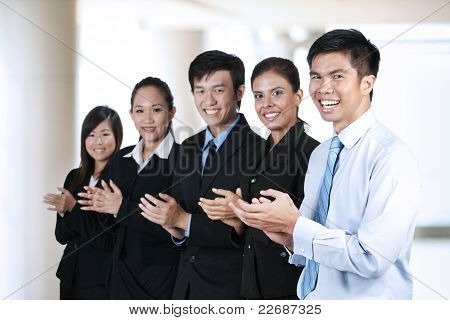 Happy Businesspeople Clapping In A Meeting